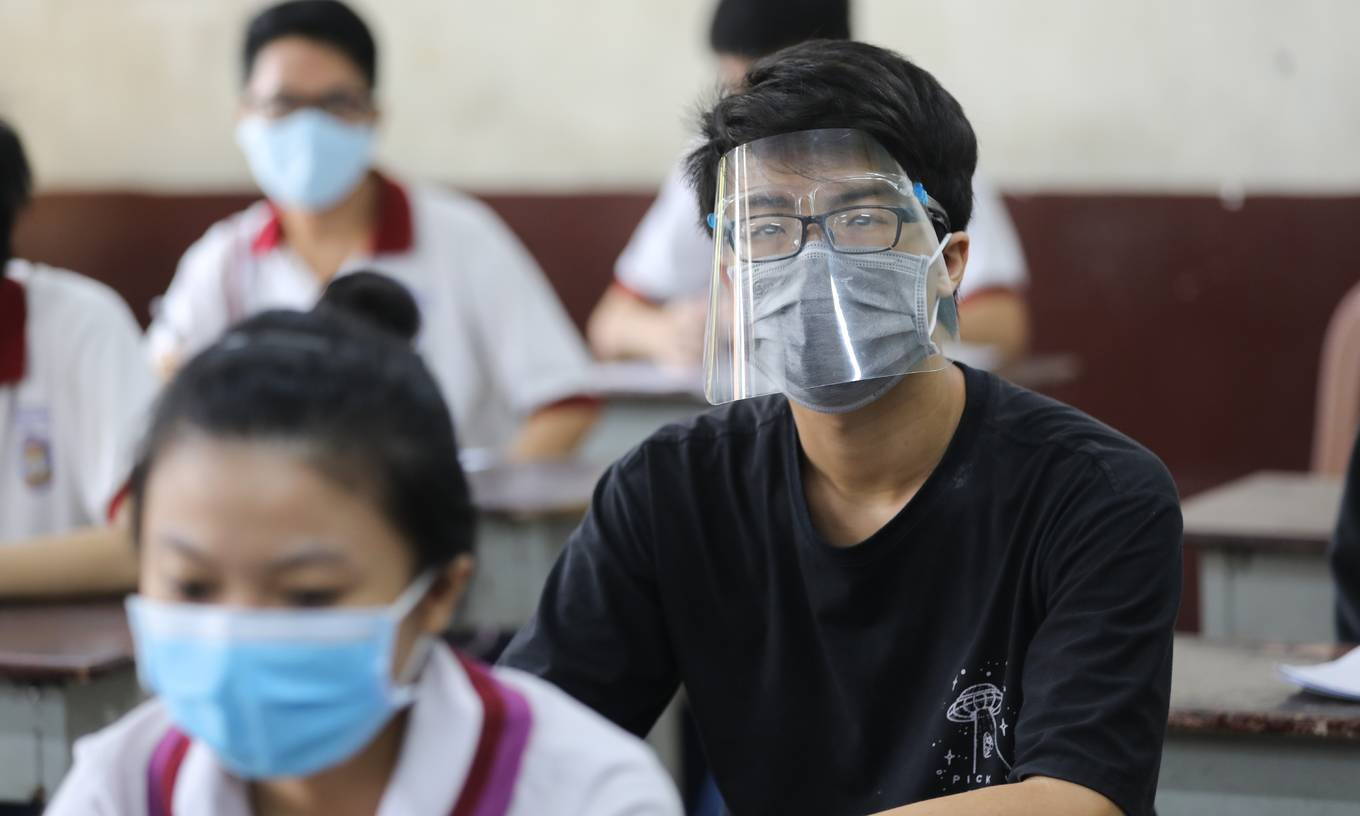 Students wear masks and face shields while participating in a national high school exam