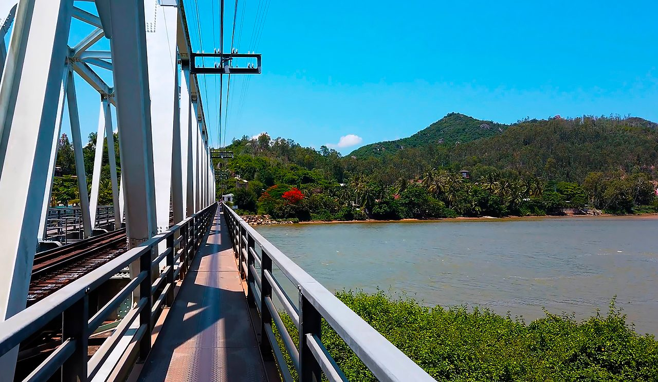 Riding a motorbike along the narrowest path on railway bridge. Nha Trang, Vietnam.